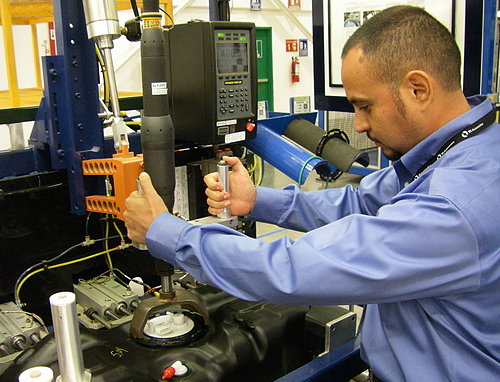 Manufacturing engineer Edgar Remes demonstrates lock ring closing of a fuel tank assembly module